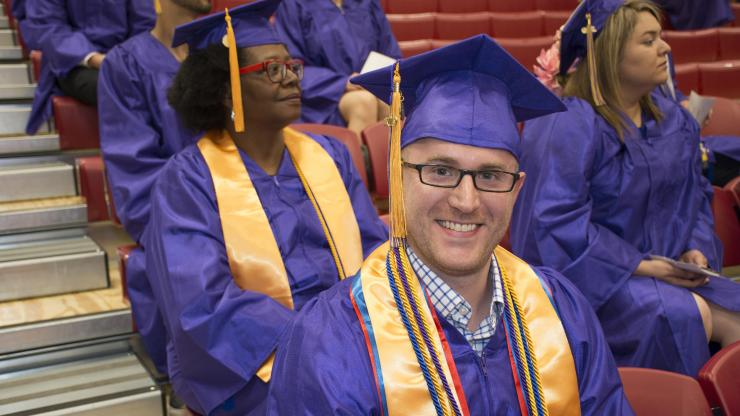 young man with purple cap and gown at commencement