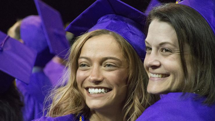 two female graduates wearing purple caps and gowns