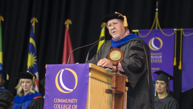 man in a black cap and gown giving a keynote commencement address