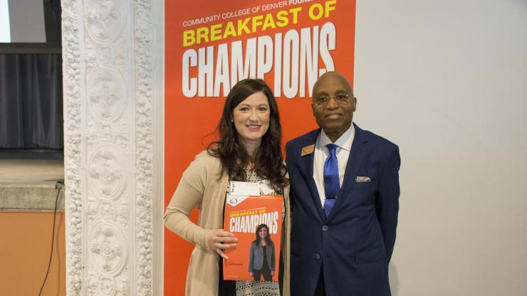 woman holding a Breakfast of Champions cereal box next to man in suit