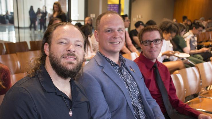 three males sitting at an awards event