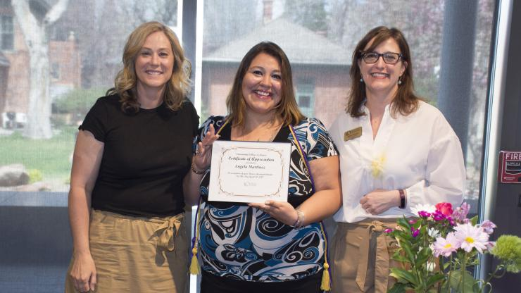 three women, one holding a certificate