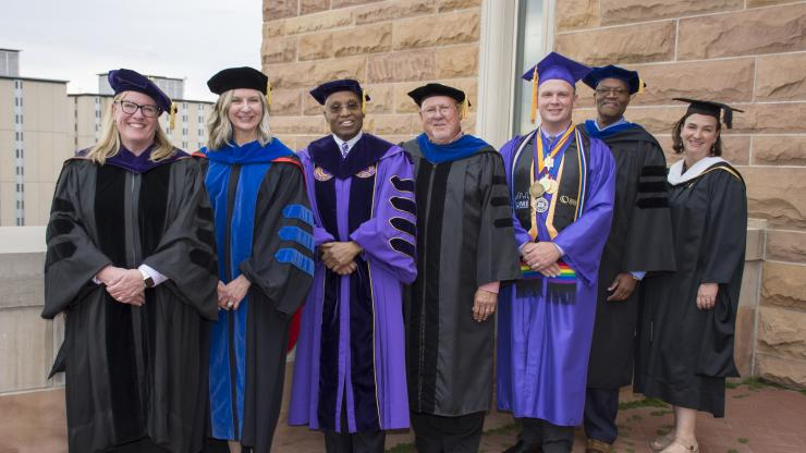 row of distinguished faculty and staff wearing caps and gowns