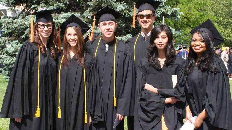 group of male and female graduates in black caps and gowns smiling