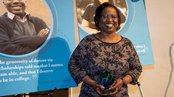 woman stands in front of sign holding an glass-blown award