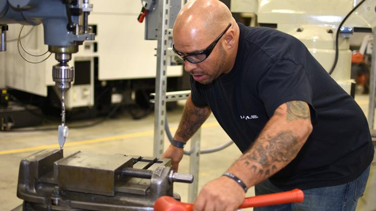 man in protective glasses learns to operate a machine
