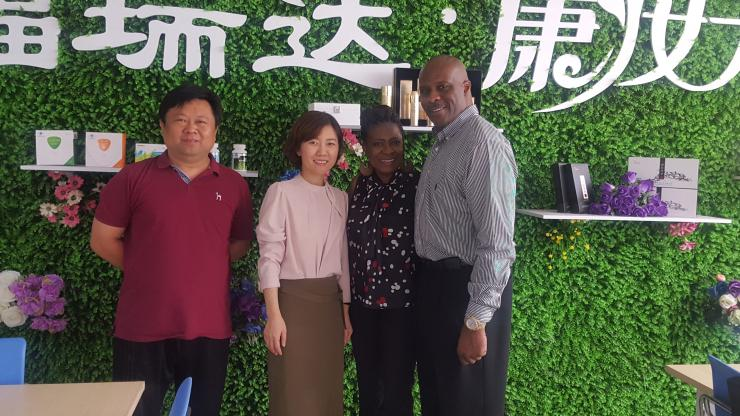 two couples standing in front of a green wall with Chinese writing on it