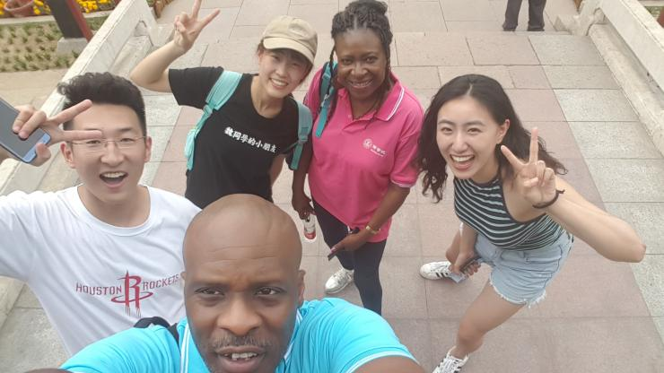 an instructor and her husband taking a selfie with three students in China
