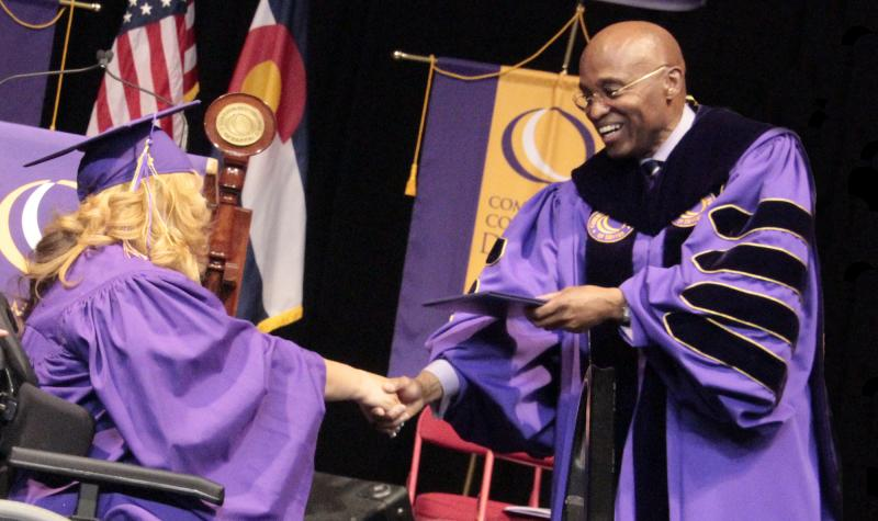 2014 female graduate in wheelchair receiving her diploma from CCD president Everette Freeman