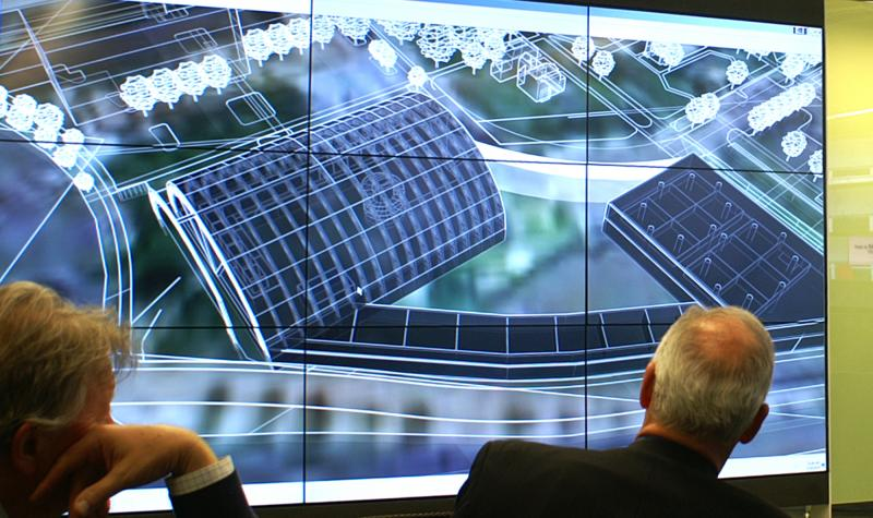 Image Of People Looking At A Large Screen With Architecture Drawings