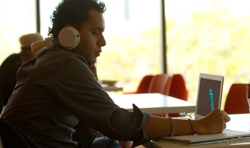 student with headphones and computer studying