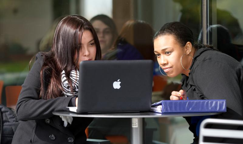 two female students work together on a computer.