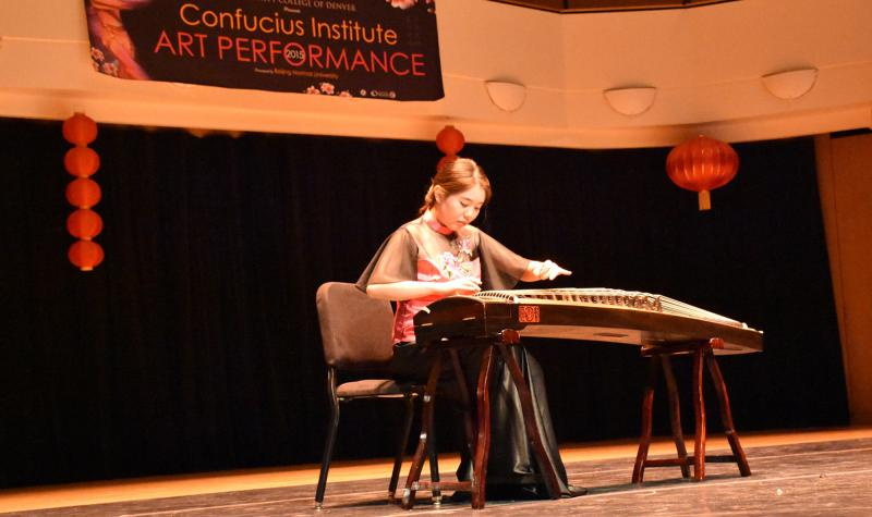 woman on stage plays ancient Chinese instrument