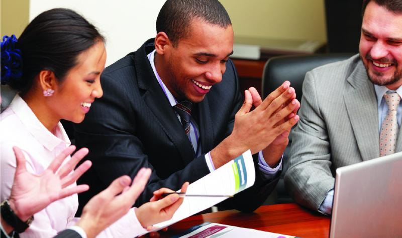 image of a group of people laughing in a business meeting