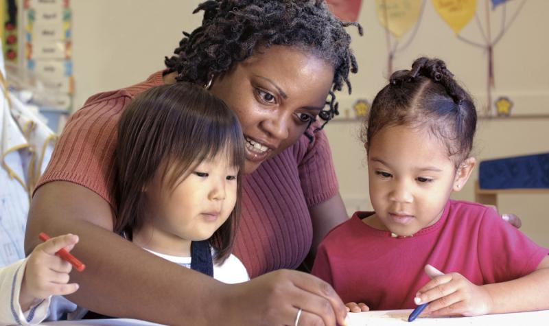 image of female teacher coloring with two pre-school girls