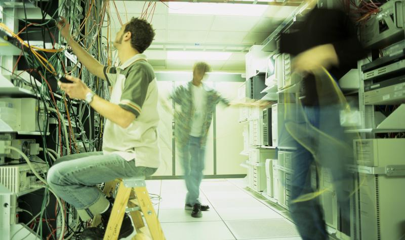 image of three people in a computer server room working on computer cables