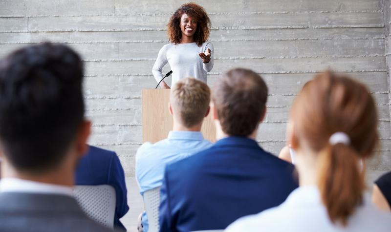 Woman standing at podium delivering speech to audience