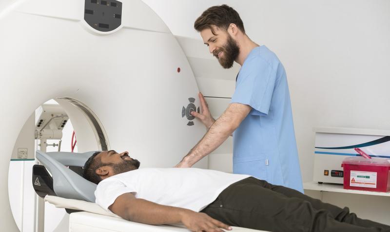 man in scrubs giving man a c-scan