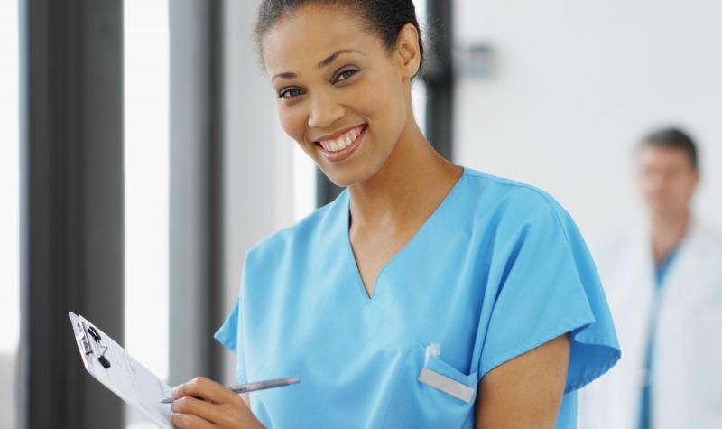 image of a young nurse wearing medical scrubs holding a clipboard