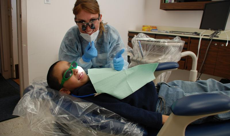 A dental hygienist giving a thumbs up with a smiling young patient