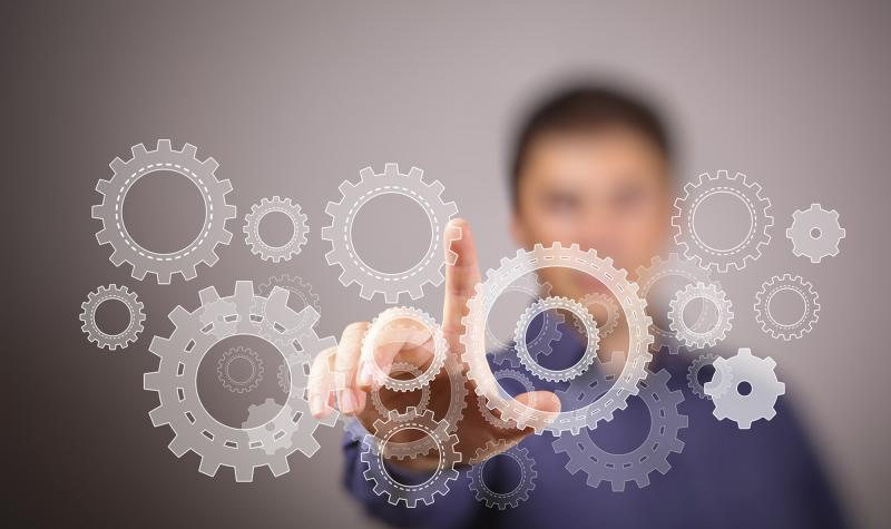 image of blurred male student reaching out to touch floating gears