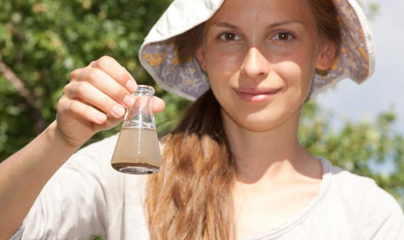 Female student outdoors with a beaker of murky water from a pond