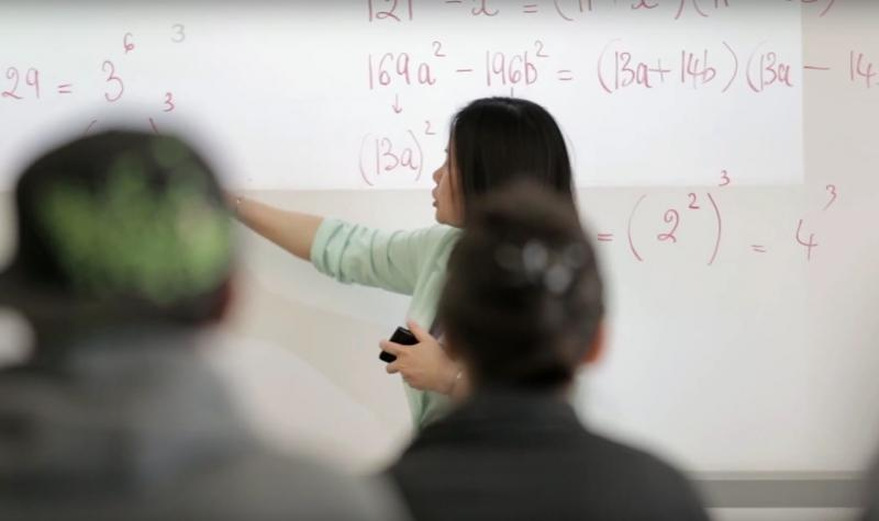 Math teacher at the white board pointing to math equations