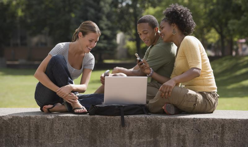 Three students looking at laptop computer and a phone outdoors