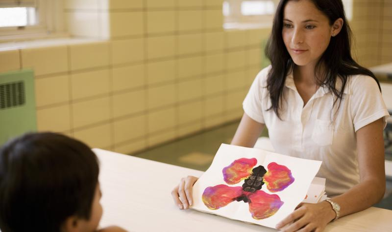 Woman showing a kid an ink blot test that looks like a butterfly
