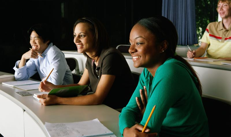 Four students smiling in a lecture hall setting