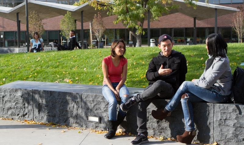 Three students in Cherry Creek Building Courtyard having a conversation