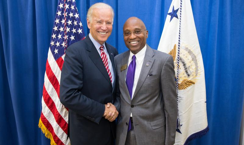 two men in suits shaking hands with American flag in background