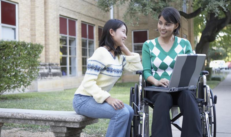 One female student sitting on a concrete bench studying with another female student in a wheelchair holding a laptop on her lap