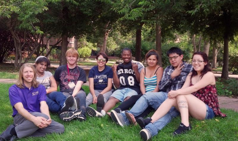Summer Bridge students sit in the grass.