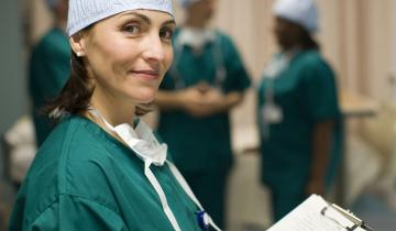 A young nurse wearing green medical scrubs holding a clipboard.