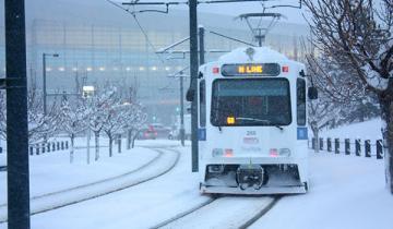 light rail train on tracks in snow
