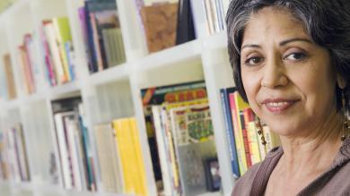 image of mature female student in front of bookshelf full of books