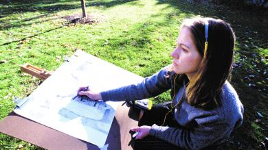 image of a female CCD student drawing on a large papaer outside on campus