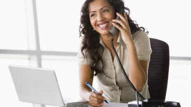 image of young woman answering phones and looking at laptop