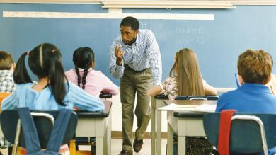 image of male elementary school teacher in front of classroom teaching