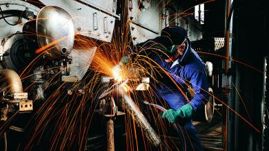Man welding a pipe with lots of sparks flying