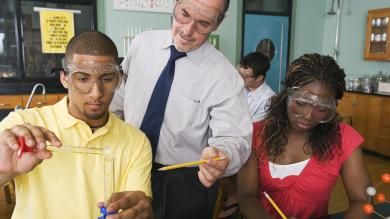 Teacher helping two students with a science experiment in a science classroom
