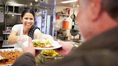Smiling young woman serving food at a homeless shelter.
