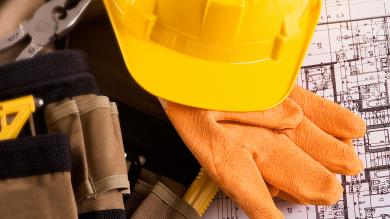 yellow hard hat, work clothes and blue prints