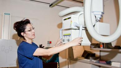 A female Radiologic Technologist prepares to take x-rays.