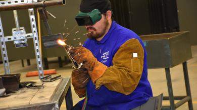 man welding while wearing protective goggles and gloves