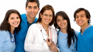 Smiling group of nurses wearing blue scrubs