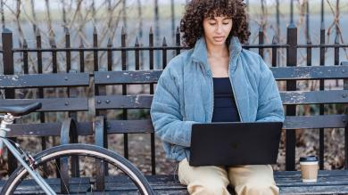 Woman sitting on park bench working on a laptop next to a coffee and a bicycle