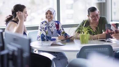 Three students coversing at a table.