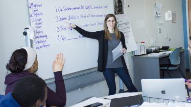 Female teacher at white board talking to two students.